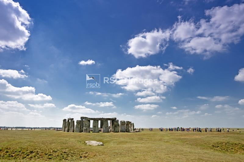 Stonehenge stone circle national monument with crowds of visitors below a s ...