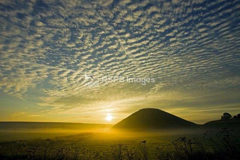 Cirrus clouds at dawn over Silbury Hill, Britain's biggest ancient monument ...