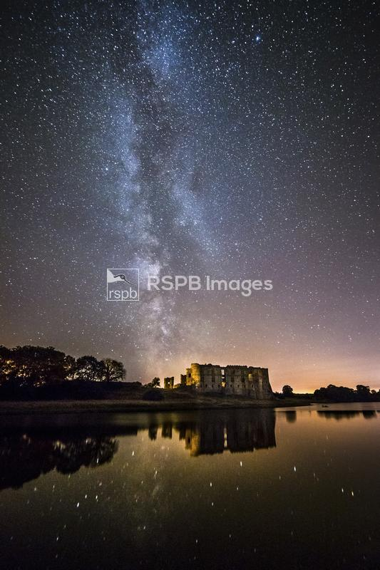 The Milky Way streaks over Carew Castle in Pembrokeshire, Wales. The spiral ...