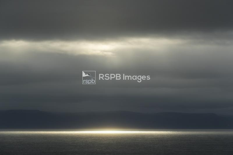 A flash of light catches the sea in bad weather on the Bristol Channel from ...
