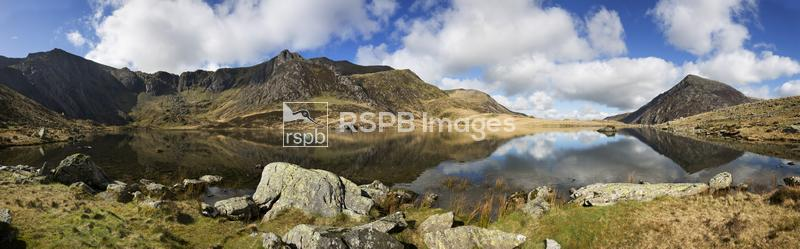 Devils Kitchen with reflections in Llyn Idwal leading round to Pen Yr Ole W ...